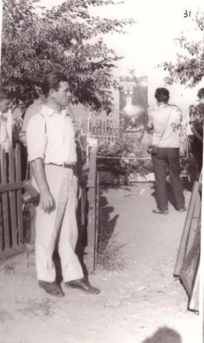 Общий вид памятника Комарова, который огражден штакетной оградкой. У калитки на фоне памятника стоит в профиль УРБП-6 Смагин Н.А